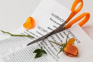 A scissor cutting a marriage certification, divorce