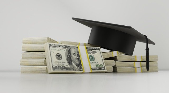 A college graduation hat and piles of dollars