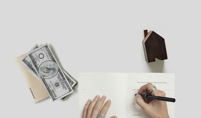 Mortgage, house model and dollar bills