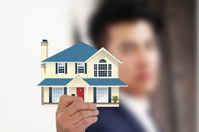 Businessman holds a house model
