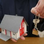 Person holds a house model and a house key