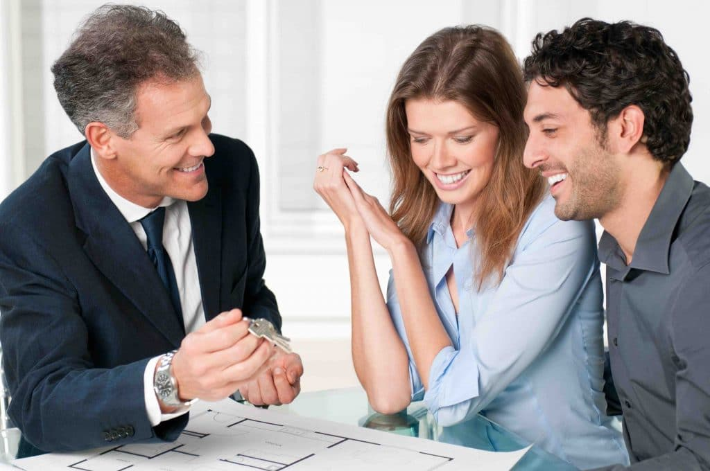 estate agent showing new home keys to a young couple