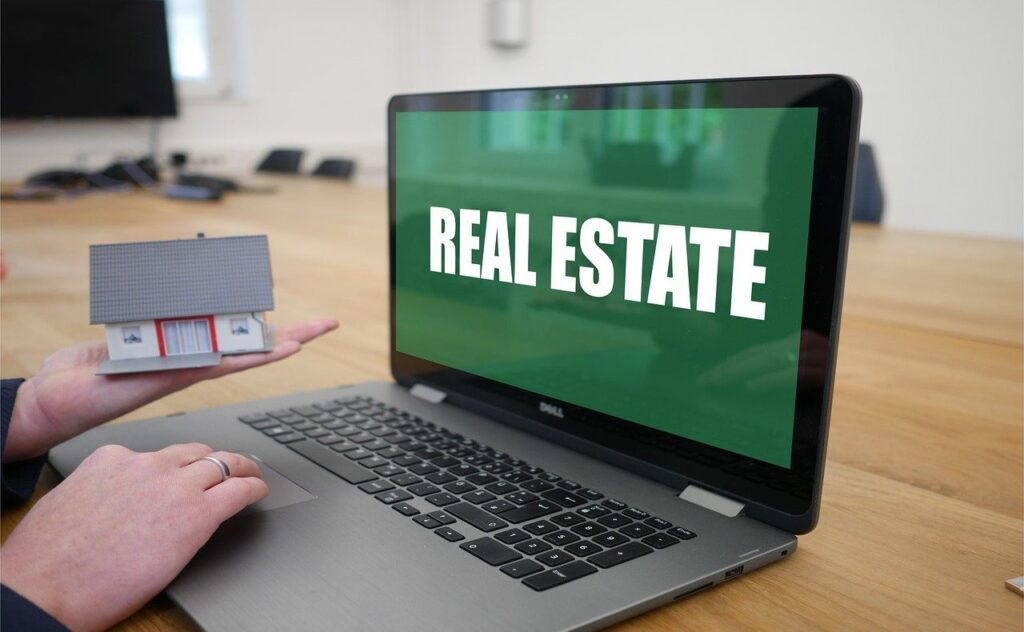 Real estate shown on computer screen, hand holds a house model