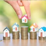 5 houses models on piles of coins, real estate market
